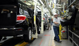 FILE - In this Wednesday, Feb. 8, 2012, file photo, Rick Twitty installs seats into 2012 Toyota Highlander vehicles at the Toyota Motor Manufacturing Indiana, Inc., plant in Princeton, Ind. On Tuesday, Jan. 24, 2017, Toyota said it will add 400 jobs and invest $600 million at the Princeton SUV factory. The announcement Tuesday comes just after President Donald Trump met with CEOs of the Detroit automakers to demand that new factories be built in the U.S. Toyota says the investment was not related to Trump and was planned before the election. (Erin McCracken/Evansville Courier & Press via AP, File)