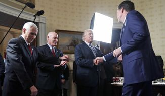 Vice President Mike Pence, left, and Secret Service Director Joseph Clancy stand as President Donald Trump shakes hands with FBI Director James Comey during a reception for inaugural law enforcement officers and first responders in the Blue Room of the White House, Sunday, Jan. 22, 2017 in Washington. (AP Photo/Alex Brandon)