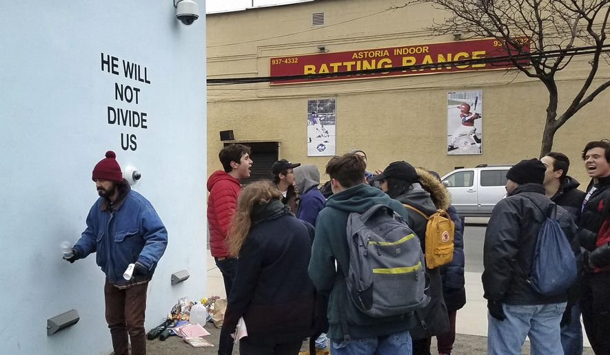 """Actor Shia LeBeouf, left, stands in front of a live-stream camera with the words """"HE WILL NOT DIVIDE US"""" posted on a wall outside of the the Museum of the Moving Image as members of the public join LeBeouf in chanting the words """"He will Not Divide Us"""" in the Queens borough of New York. LaBeouf has spent the first four days of the Trump presidency swaying, dancing and chanting, along with anyone who wants to join in. The project by LeBeouf and two other artists opened on Jan. 20 and is expected to go for 4 years, or for """"the duration of the presidency."""" (AP Photo/Deepti Hajela)"""