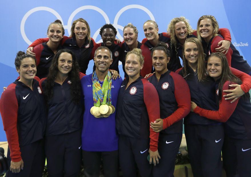 FILE - In this Aug. 19, 2016, file photo, members of United States women water polo team pose with a coach Adam Krikorian during the medals ceremony at the 2016 Summer Olympics in Rio de Janeiro, Brazil. U.S. water polo coaches Adam Krikorian and Dejan Udovicic are staying on for the 2020 Tokyo Olympics. (AP Photo/Sergei Grits, File)