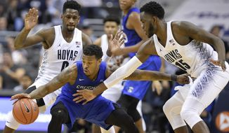 Georgetown guard L.J. Peak, left, and center Jessie Govan (15) vie for the ball against Creighton guard Marcus Foster, center, during the second half of an NCAA college basketball game, Wednesday, Jan. 25, 2017, in Washington. Georgetown won 71-51. (AP Photo/Nick Wass)