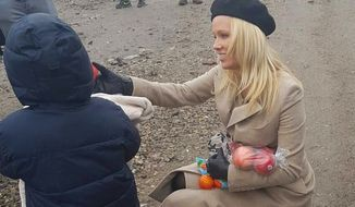 In this handout picture provided by PETA, actress Pamela Anderson delivers some presents to children in the Grande-Synthe refugee camp in Dunkerque, northern France, Wednesday, Jan. 25, 2017. (AP Photo)