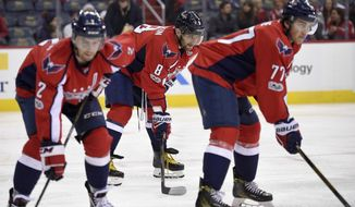 Washington Capitals left wing Alex Ovechkin (8), of Russia, looks on next to defenseman Matt Niskanen (2) and right wing T.J. Oshie (77) during the second period of an NHL hockey game against the Carolina Hurricanes, Monday, Jan. 23, 2017, in Washington. (AP Photo/Nick Wass)