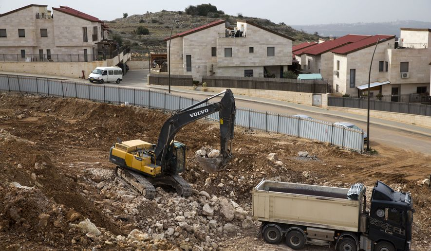 Heavy machinery work at a construction site in the West Bank Jewish settlement of Ariel, Wednesday, Jan. 25, 2017. Israel announced plans Tuesday to build 2,500 more settler homes on the West Bank, moving to step up construction just days after the swearing-in of Donald Trump brought to power a U.S. administration seen as friendly to the settlement movement. (AP Photo/Ariel Schalit)
