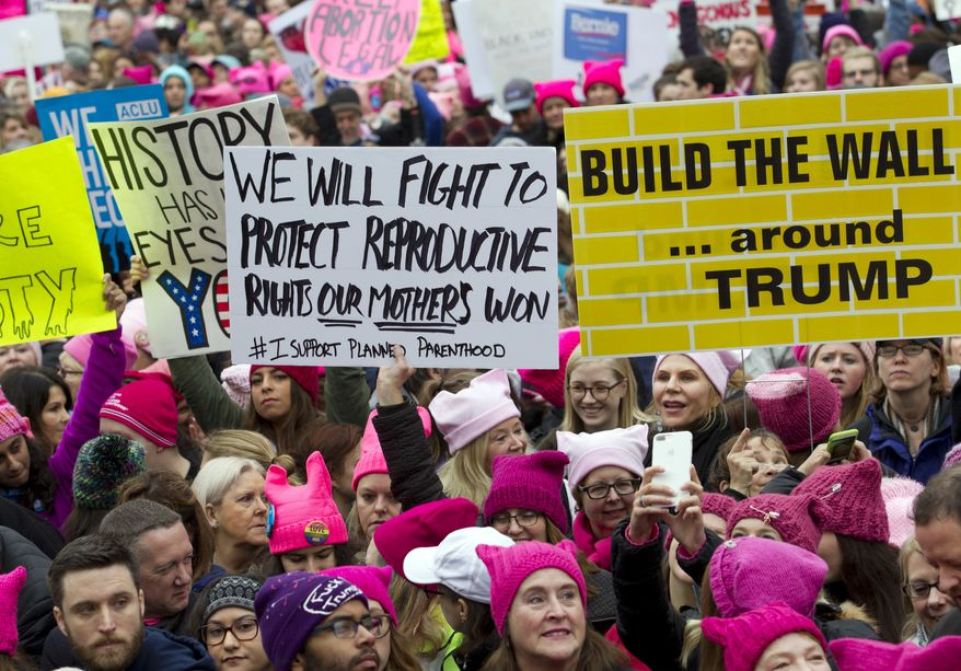 FILE - In this Saturday, Jan. 21, 2017 file photo, women with bright pink hats and signs begin to gather early and are set to make their voices heard on the first full day of Donald Trump's presidency, in Washington. The owner of a Tennessee knitting store doesn't want anyone buying its yarn for arts and crafts for the women's movement, following weekend protests by marchers in knitted, pointy-eared hats. The Tennessean newspaper reported that the comments Tuesday on the Facebook page of The Joy of Knitting store in Franklin drew both support and vows of a boycott. (AP Photo/Jose Luis Magana, File)