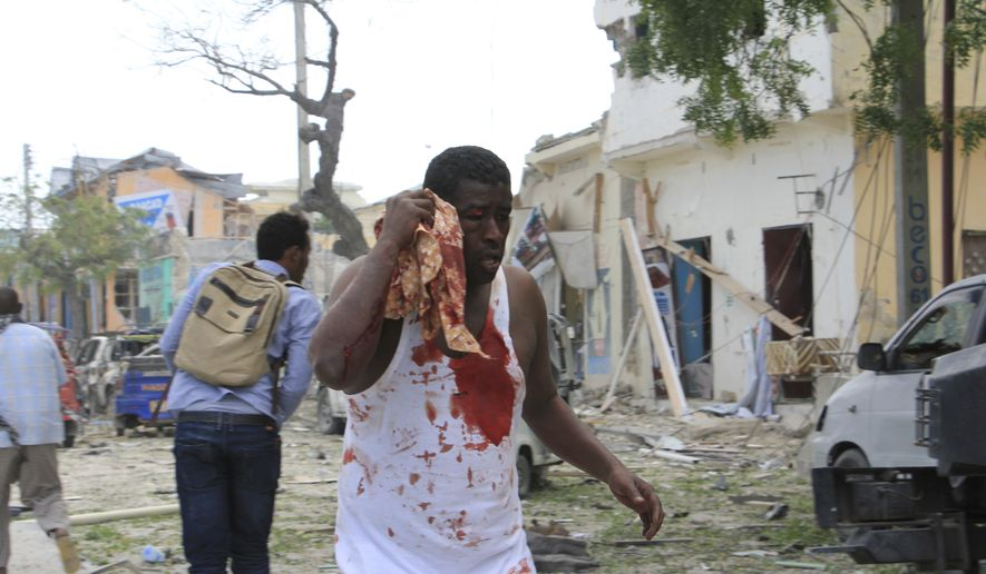 A wounded Somali man walks to safety after a car bomb attack on a hotel in Mogadishu, Somalia, Wednesday, Jan 25, 2017. Gunmen from Somalia's violent Islamic extremist rebels fought their way into a hotel in the Somali capital after a suicide car bomb exploded at its gates, a police officer said Wednesday. (AP Photo/Farah Abdi Warsameh)