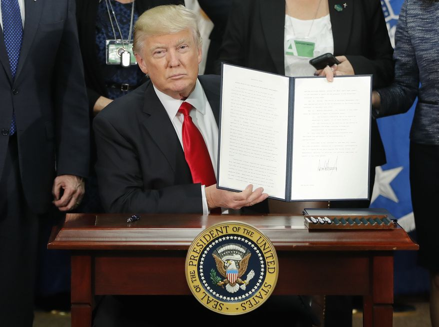 President Donald Trump holds up an executive order for border security and immigration enforcement improvements after signing the order during a visit to the Homeland Security Department headquarters in Washington, Wednesday, Jan. 25, 2017. (AP Photo/Pablo Martinez Monsivais)