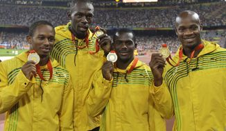 In this Saturday, Aug. 23, 2008, file photo, Jamaica's men's 4x100 meters relay team, from left, Michael Fraser, Usain Bolt, Nesta Carter and Asafa Powell show their gold medals during the athletics competitions in the National Stadium at the Beijing 2008 Olympics in Beijing. Usain Bolt has been stripped of one of his nine Olympic gold medals, Wednesday Jan. 25, 2017, in a doping case involving teammate Nesta Carter. (AP Photo/Petr David Josek, File)