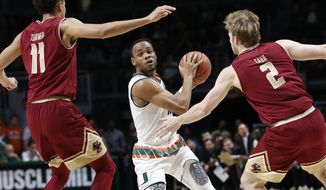 Miami guard Bruce Brown, center, looks for an open teammate past Boston College forward A.J. Turner (11) and forward Connar Tava (2) during the first half of an NCAA college basketball game, Wednesday, Jan. 25, 2017, in Coral Gables, Fla. (AP Photo/Wilfredo Lee)