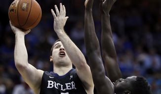 Butler forward Andrew Chrabascz, left, shoots against Seton Hall forward Ismael Sanogo during the first half of an NCAA college basketball game, Wednesday, Jan. 25, 2017, in Newark, N.J. (AP Photo/Julio Cortez)
