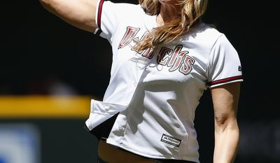 FILE - In this April 12, 2015, file photo, gold medalist Jennie Finch throws out a ceremonial first pitch prior to a baseball game between the Arizona Diamondbacks and the Los Angeles Dodgers, in Phoenix. Finch is pitching youth softball this spring as an ambassador for Major League Baseball.The commissioner's office announced Wednesday, Jan. 25, 2017, that she'll join Cal Ripken Jr. and Ken Griffey Jr. as MLB youth ambassadors.(AP Photo/Ross D. Franklin, File)
