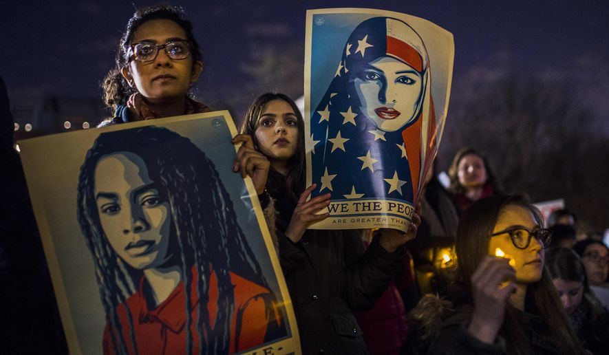 Protesters listen to an speaker as the hold signs during a rally against President Donald Trump's order cracking down on immigrants living in the US at Washington Square Park in New York, Wednesday, Jan. 25, 2017. (AP Photo/Andres Kudacki)