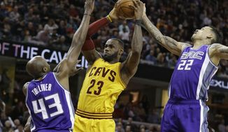 Sacramento Kings' Anthony Tolliver (43) and Matt Barnes (22) defend Cleveland Cavaliers' LeBron James (23) during the second half of an NBA basketball game, Wednesday, Jan. 25, 2017, in Cleveland. The Kings won 116-112. (AP Photo/Tony Dejak)