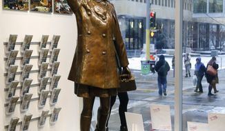 """A single rose sits by the life-size bronze statue of Mary Tyler Moore at the Minneapolis Visitor Center, Wednesday, Jan. 25, 2017. Moore, 80, died Wednesday. The statue depicts her tossing her tam into the air as she did in the opening credits of """"The Mary Tyler Moore Show."""" (AP Photo/Jim Mone)"""