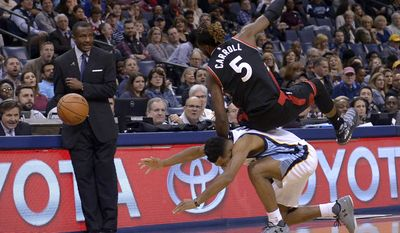 Toronto Raptors forward DeMarre Carroll (5) falls over Memphis Grizzlies guard Andrew Harrison as Raptors head coach Dwane Casey looks on in the first half of an NBA basketball game, Wednesday, Jan. 25, 2017, in Memphis, Tenn. (AP Photo/Brandon Dill)