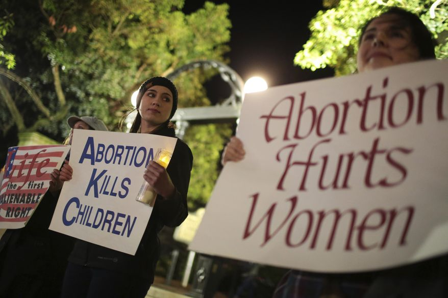 Ariana Marsh, center, and Katie Davis, right, participate in a pro-life candle light vigil organized by Students for Life at UGA held to protest Roe v. Wade at the University of Georgia Arch in Athens, Ga., in this Tuesday, Jan. 24, 2017, file photo. (John Roark/Athens Banner-Herald via AP) ** FILE **