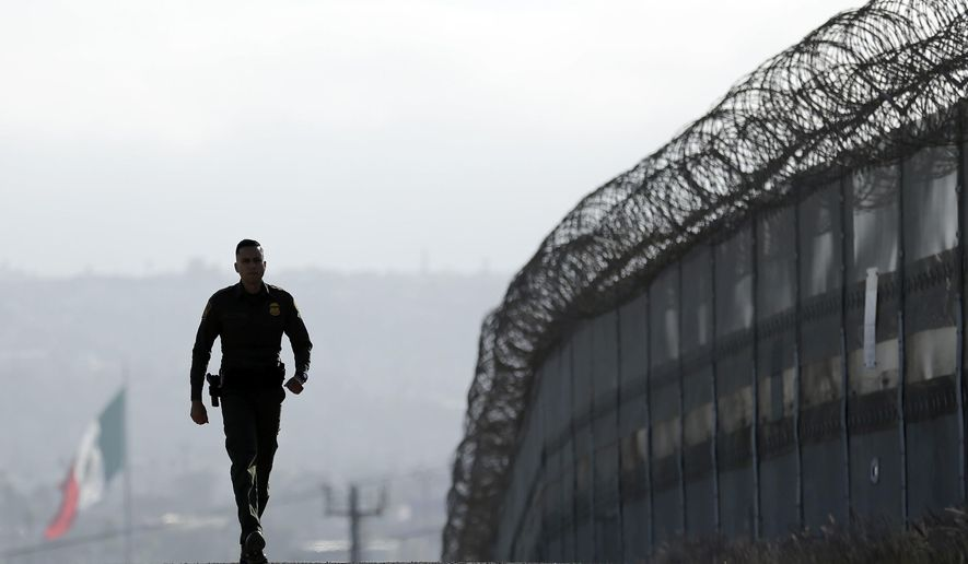 In this June 22, 2016, file photo, Border Patrol agent Eduardo Olmos walks near the secondary fence separating Tijuana, Mexico, background, and San Diego in San Diego. U.S. President Donald Trump will direct the Homeland Security Department to start building a wall at the Mexican border. (AP Photo/Gregory Bull, file)