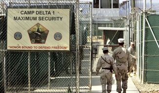 In this June 27, 2006 file photo, reviewed by a US Department of Defense official, US military guards walk within Camp Delta military-run prison, at the Guantanamo Bay US Naval Base, Cuba.  (AP Photo/Brennan Linsley, file)
