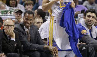 Golden State Warriors' Stephen Curry, smiles as he watches the action from the bench in the first half of an NBA basketball game against the Charlotte Hornets in Charlotte, N.C., Wednesday, Jan. 25, 2017. (AP Photo/Chuck Burton)