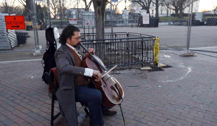 Karim Wasfi, the former conductor of the Baghdad Symphony, plays his cello is Lafayette Park near a protest about President Donald Trump's immigration policies, Wednesday, Jan. 25, 2017 in Washington. The half-Iraqi, half-Egyptian cellist and founder of an organization called Peace Through Arts played serene classical tunes. (AP Photo/Alex Brandon)