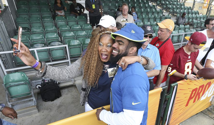 Dallas Cowboys running back Ezekiel Elliott (21) poses for a photo with a fan after NFC practice for the 2017 Pro Bowl, Thursday, Jan. 26, 2017 in Lake Buena Vista, Fla. (AP Photo/Doug Benc)
