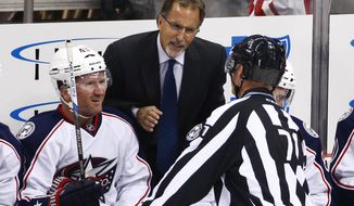 FILE - In this Oct. 8, 2016, file photo, Columbus Blue Jackets head coach John Tortorella, center, talks with linesman Brad Kovachik (71), with Scott Hartnell, left, listening during the first period of a preseason NHL hockey game against the Pittsburgh Penguins in Pittsburgh. Tortorella has returned to Ohio because of a family emergency, keeping him out of both Thursday night's game with Nashville and the NHL All-Star Game this weekend. (AP Photo/Gene J. Puskar, File)