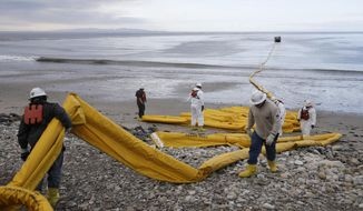 FILE - In this May 21, 2015 file photo, workers prepare an oil containment boom at Refugio State Beach, north of Goleta, Calif. The clean-up for the largest coastal oil spill in California in 25 years, which the U.S. Environmental Protection Agency helped oversee, climbed to $92 million. The former head of President Donald Trump's transition team at the Environmental Protection Agency says he expects the new administration to seek significant budget and staff cuts for the department. (AP Photo/Jae C. Hong, File)