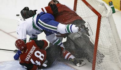Arizona Coyotes left wing Jordan Martinook (48) and Vancouver Canucks right wing Jack Skille (9) crash in to Coyotes goalie Mike Smith, right, during the second period of an NHL hockey game Thursday, Jan. 26, 2017, in Glendale, Ariz. (AP Photo/Ross D. Franklin)