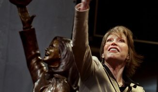 """In the May 8, 2002 photo, actress Mary Tyler Moore, standing beside a statue depicting her legendary tam toss, tossed another tam as the bronze statue of her was unveiled on Nicollet Mall in Minneapolis. Moore, 80, died Wednesday, Jna. 25, 2017. The statue depicts her tossing her tam into the air as she did in the opening credits of """"The Mary Tyler Moore Show."""" (Jerry Holt/Star Tribune via AP)"""