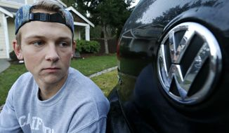 In this Tuesday, Jan. 24, 2017, photo, David Derkach poses for a photo with his Volkswagen Golf, at his home in Federal Way, Wash. Derkach has faced delays in getting Volkswagen to buy back his diesel-engine vehicle following VW's emissions-cheating scandal. (AP Photo/Ted S. Warren)
