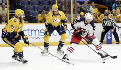 Columbus Blue Jackets left wing Brandon Saad (20) moves the puck as he is defended by Nashville Predators' Matt Irwin (52) during the first period of an NHL hockey game Thursday, Jan. 26, 2017, in Nashville, Tenn. (AP Photo/Mark Humphrey)