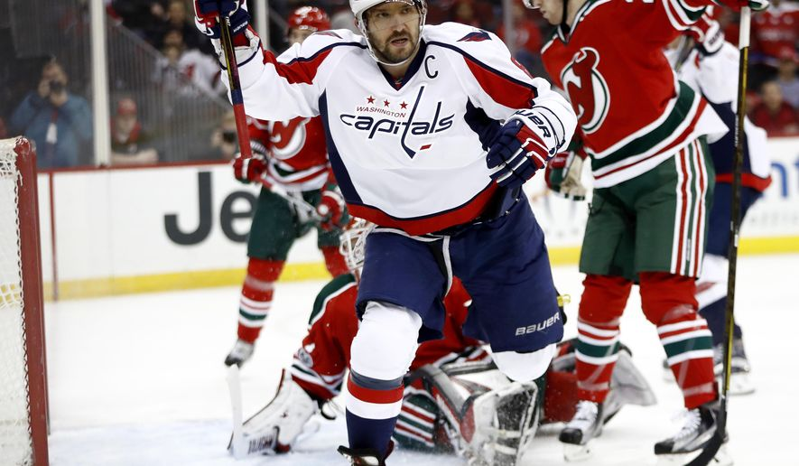 Washington Capitals left wing Alex Ovechkin, front, of Russia, celebrates after scoring a goal against the New Jersey Devils during the first period of an NHL hockey game, Thursday, Jan. 26, 2017, in Newark, N.J. (AP Photo/Julio Cortez)
