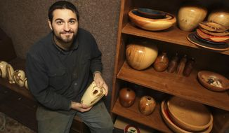 ADVANCE FOR USE SATURDAY, JAN. 28, 2017 AND THEREAFTER - In this Jan. 13,  2017 photo Jeremy Williams is seen with samples of his wood turning in Shelbyville, Ill. Williams' medium is dead wood, and that wood is often twisted, holed and decorated by the ravages of disease that he turns into artsy shapes and patterning. (Jim Bowling/Herald & Review via AP)