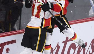 Calgary Flames left wing Johnny Gaudreau (13) celebrates his overtime goal with center Mikael Backlund (11) during an NHL hockey game against the Ottawa Senators on Thursday, Jan. 26, 2017, in Ottawa, Ontario. (Sean Kilpatrick/The Canadian Press via AP)