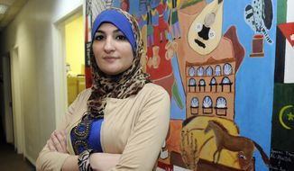 In this Dec. 29, 2011, file photo, Linda Sarsour, executive director of the Arab American Association of New York, poses for photos in front of a canvas painted by the association's youth group at its headquarters in the Brooklyn borough of New York. (AP Photo/Henny Ray Abrams, File)
