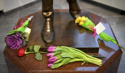 """Flowers were placed at the base of  at the base of a life-size bronze statue of Mary Tyler Moore at the Minneapolis Visitor Center Wednesday, Jan. 25, 2017. Moore, 80, died Wednesday. The statue depicts her tossing her tam into the air as she did in the opening credits of """"The Mary Tyler Moore Show"""" which featured Moore as Mary Richards working for a fictional Minneapolis television station. (Aaron Lavinsky/Star Tribune via AP)"""