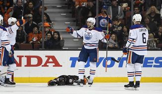 Edmonton Oilers center Leon Draisaitl, second from right, of Germany, celebrates his goal with left wing Patrick Maroon, left, and defenseman Adam Larsson, right, of Sweden as Anaheim Ducks defenseman Kevin Bieksa lies on the ice during the second period of an NHL hockey game, Wednesday, Jan. 25, 2017, in Anaheim, Calif. (AP Photo/Mark J. Terrill)