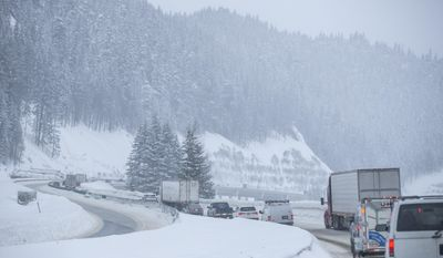 In this Monday, Jan. 9, 2017 photo, cars move slowly after a semi-truck rollover accident closed Interstate 90 eastbound for a few hours at Snoqualmie Pass, Wash.  Snoqualmie Pass averages 28,000 vehicles a day, so keeping roads open can be a challenging goal in the winter weather.  (Bettina Hansen /The Seattle Times via AP)