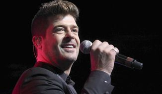 FILE - In this Aug. 7, 2015 file photo, Robin Thicke performs during the Steve Harvey Morning Show live broadcast at the Georgia World Congress Center in Atlanta. A judge has ordered Thicke to stay away from his ex-wife, actress Paula Patton and only have monitored visits with his 6-year-old son. Los Angeles Superior Court Judge Colin Leis issued the temporary restraining order on Thursday, Jan. 26, 2017, after Patton accused the singer of physically abusing her during their marriage, which ended in March 2015. (Photo by Robb D. Cohen/Invision/AP, File)