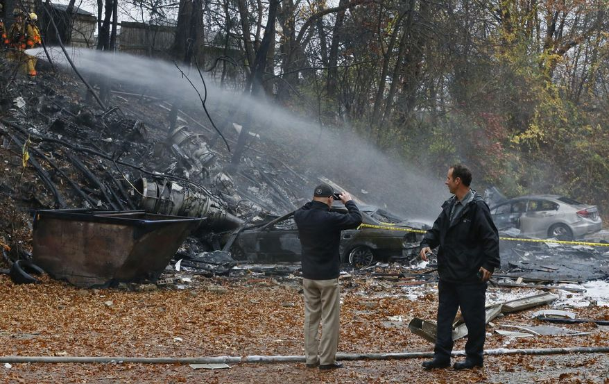 FILE - In a Tuesday, Nov. 10, 2015 file photo, Terry Ellis, left, takes photos as firefighters work at the scene where authorities say a small business jet crashed into an apartment building in Akron, Ohio. A second lawsuit has been filed seeking damages over the deadly crash of a corporate jet into the Ohio apartment building. The Akron Beacon Journal reports a resident of an apartment destroyed in the 2015 crash is suing the Florida company that owned the plane and the estates of the two pilots who died. (Ed Suba Jr./Akron Beacon Journal via AP, File)