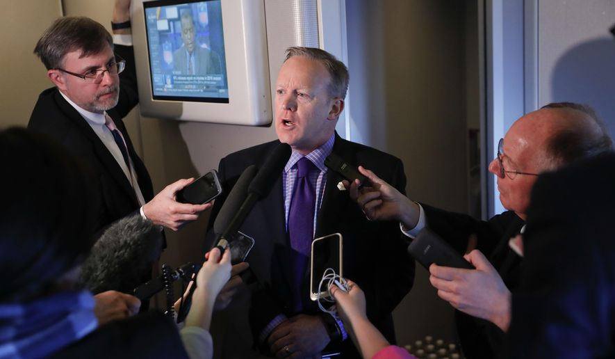 """White House press secretary Sean Spicer speaks to reporters on Air Force One en route to Andrews Air Force Base, Thursday, Jan. 26, 2017, from Philadelphia. Spicer says that taxing imports from Mexico would generate $10 billions a year and """"easily pay for the wall."""" (AP Photo/Pablo Martinez Monsivais)"""