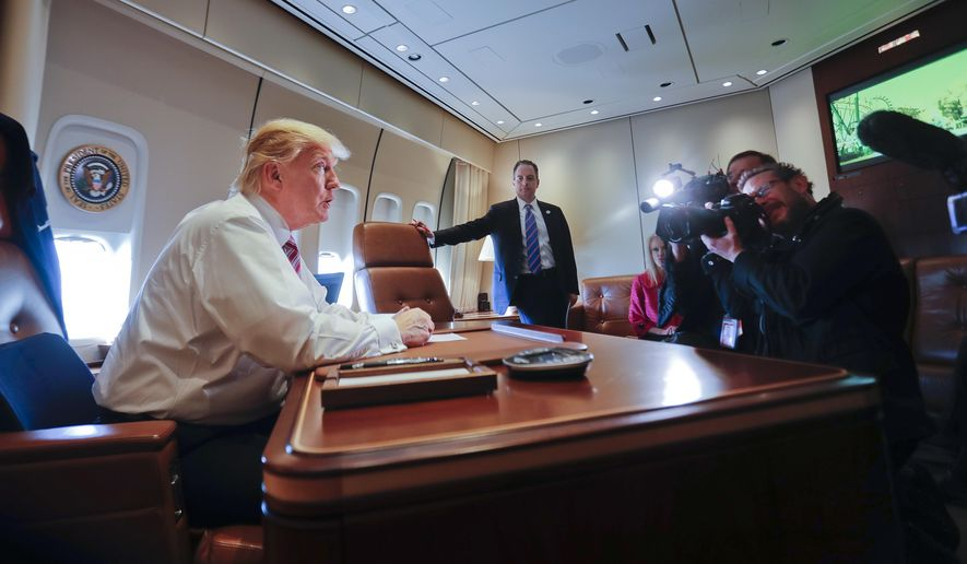 President Donald Trump sits at his desk on Air Force One upon his arrival at Andrews Air Force Base, Md., Thursday, Jan. 26, 2017. At the center is  Chief of Staff Reince Priebus. (AP Photo/Pablo Martinez Monsivais)