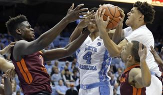 North Carolina's Isaiah Hicks (4) and Justin Jackson, right, struggle for possession of the ball with Virginia Tech's Khadim Sy (2) and Justin Robinson, right, during the first half of an NCAA college basketball game in Chapel Hill, N.C., Thursday, Jan. 26, 2017. (AP Photo/Gerry Broome)