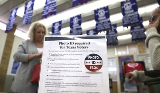 In this March 1, 2016, file photo, a sign tells voters of voter ID requirements before participating in the primary election at Sherrod Elementary school in Arlington, Texas. (AP Photo/LM Otero, File)