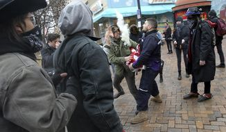 In this Thursday, Jan. 26, 2017 photo, Matt Uhrin, center right, confronts Andrew Alemao as he gathers with fellow protesters to burn American flags on the pedestrian mall in Iowa City, Iowa.  (David Srivner /Iowa City Press-Citizen via AP)