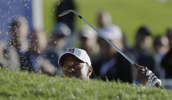 Tiger Woods hits out of a bunker on the 17th hole of the south course during the first round of the Farmers Insurance Open golf tournament Thursday, Jan. 26, 2017, at Torrey Pines Golf Course in San Diego. (AP Photo/Gregory Bull)