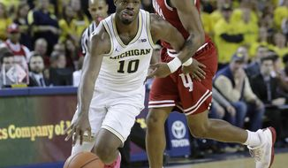Michigan guard Derrick Walton Jr. (10) drives around Indiana guard Devonte Green during the second half of an NCAA college basketball game, Thursday, Jan. 26, 2017, in Ann Arbor, Mich. (AP Photo/Carlos Osorio)