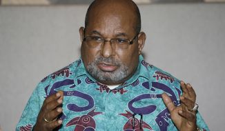 Papua Governor Lukas Enembe gestures during a press conference in Jakarta, Indonesia, Friday, Jan. 27, 2017. Enembe says they have won a lawsuit in a claim against the local unit of a giant U.S. owned gold and copper mine for $376 million related to surface water taxes. (AP Photo/Tatan Syuflana)