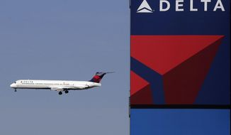 In this Saturday, April 6, 2013, file photo, a Delta Airlines jet flies past the company's billboard at Citi Field, in New York. A Massachusetts man who authorities say assaulted a Muslim airline employee at New York's Kennedy Airport is facing hate crime charges. (AP Photo/Mark Lennihan, File)