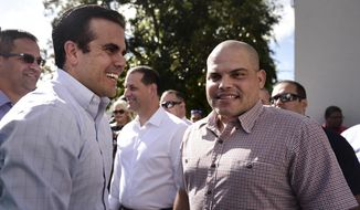 "Puerto Rico Gov. Ricardo Rossello, left, greets former Major League Baseball player Ivan ""Pudge"" Rodriguez, in his hometown Vega Baja, Puerto Rico, Friday, Jan. 27, 2017. (AP Photo/Carlos Giusti) ** FILE **"